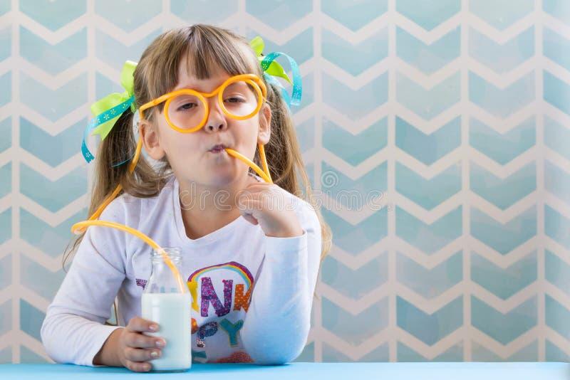 Trinkmilch des lustigen Kindermädchens mit Glasstroh auf blauem backgr stockbild