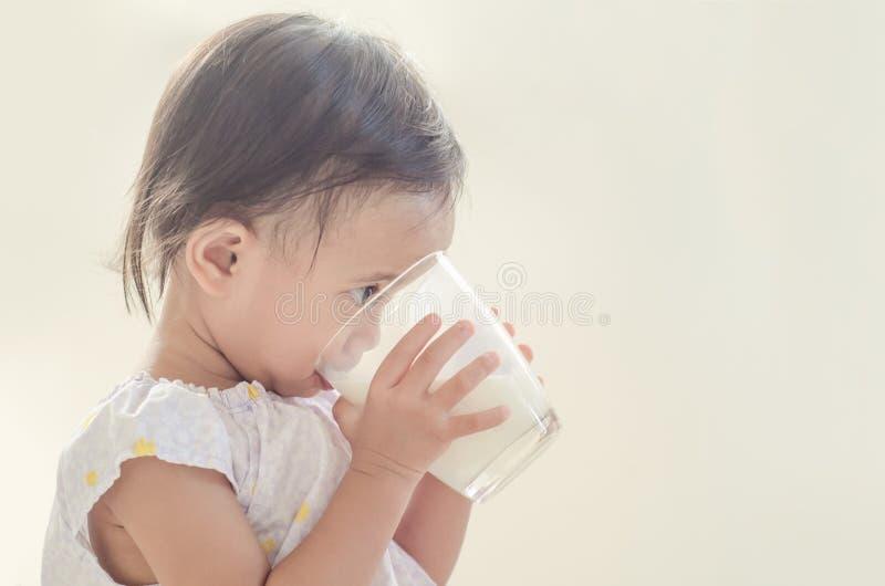 Trinkmilch des netten asiatischen Kleinkindmädchens vom großen Glas auf weißem Ba stockfoto