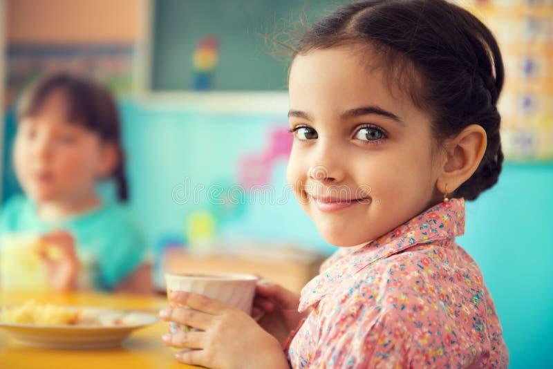 Trinkmilch des netten hispanischen Mädchens in der Schule lizenzfreies stockbild