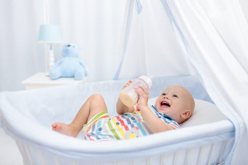 Trinkmilch des Schätzchens Junge mit Formelflasche im Bett lizenzfreie stockfotos