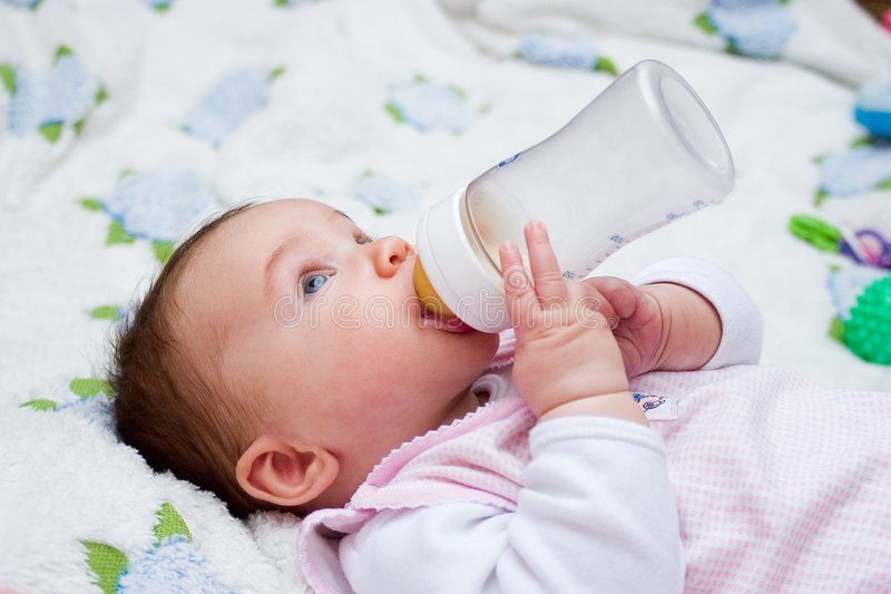 Trinkmilch des Schätzchens von der Flasche stockfotografie