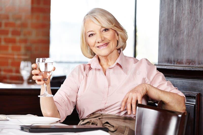 Trinkwasser der älteren Frau stockfotos