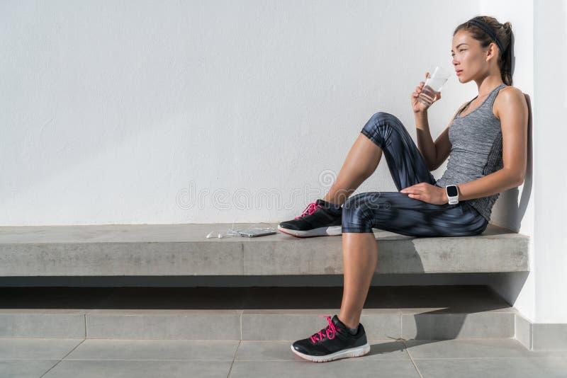 Trinkwasser der Eignungsathletenfrau auf Training stockbild