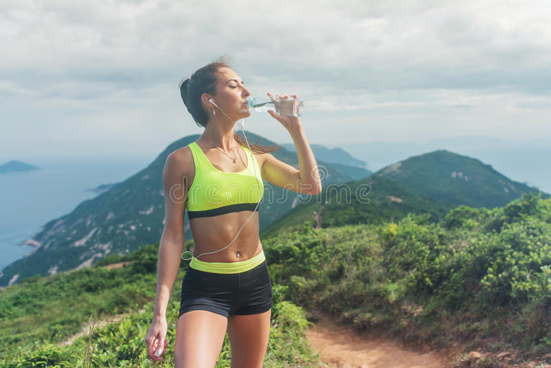 Trinkwasser der Eignungsfrau von einer Flasche, die nachdem das Hören Musik sich entspannt, die, herein auf grasartigem Berg steh lizenzfreie stockfotografie