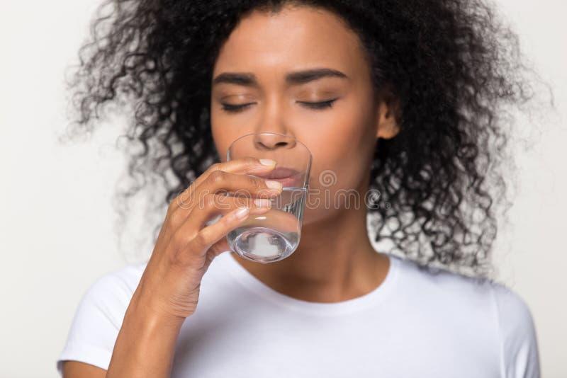 Trinkwasser der gesunden durstigen afrikanischen Frau lokalisiert auf weißem Hintergrund lizenzfreies stockfoto
