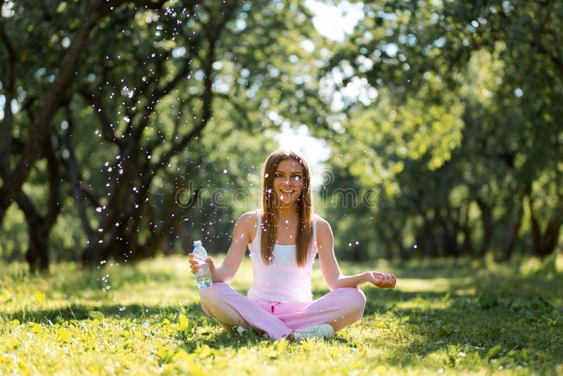 Trinkwasser der gesunden Frau von einer Flasche und Sitzen auf einem Gras nach Übungs- und Praxisyoga am Park stockbilder