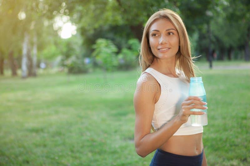 Trinkwasser der herrlichen athletischen Frau am Park lizenzfreies stockfoto