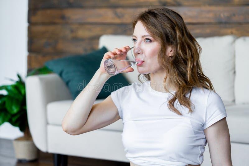 Trinkwasser der jungen Blondine, nach ausdehnende Yoga?bungen zu Hause tun stockfotos