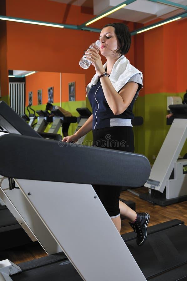 Trinkwasser der jungen Frau beim Ausarbeiten stockfotos