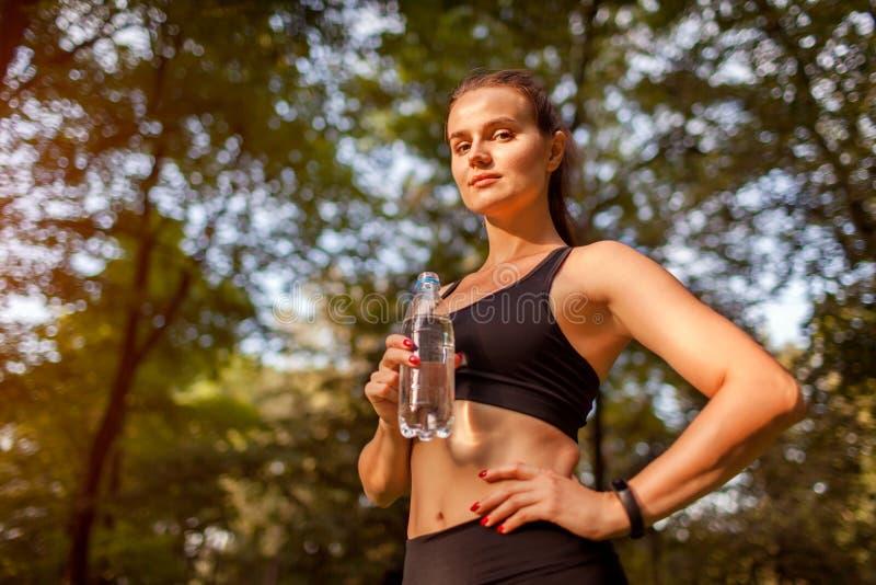 Trinkwasser der jungen sportiven Frau nach Training im Sommerpark Gesunde Lebensart lizenzfreie stockfotos
