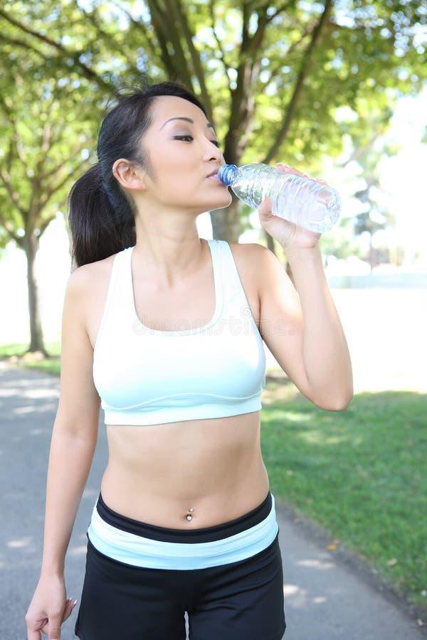 Trinkwasser der recht asiatischen Frau nach Übung lizenzfreies stockbild