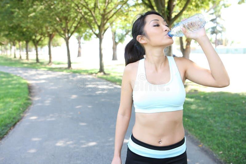 Trinkwasser der recht asiatischen Frau nach Übung stockbilder