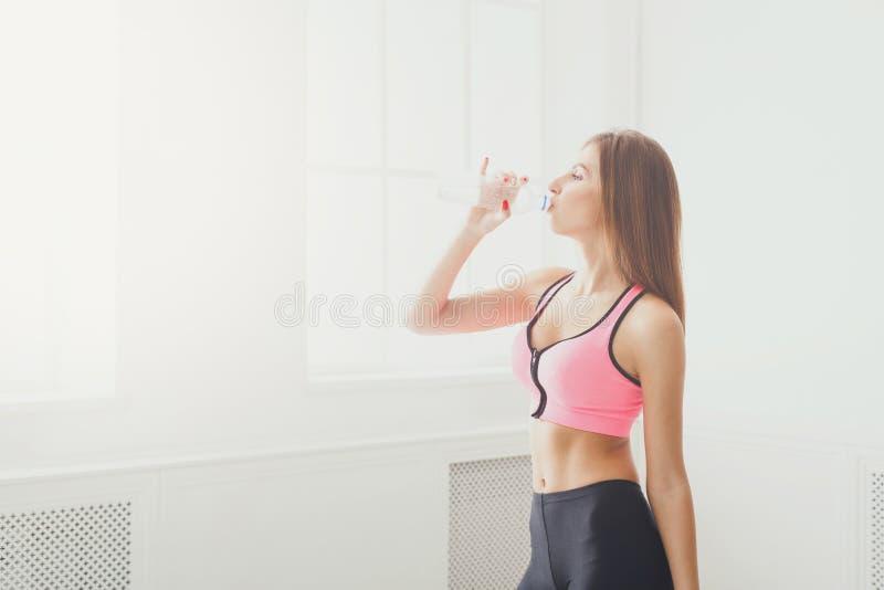 Trinkwasser der schönen jungen Sportfrau stockbilder