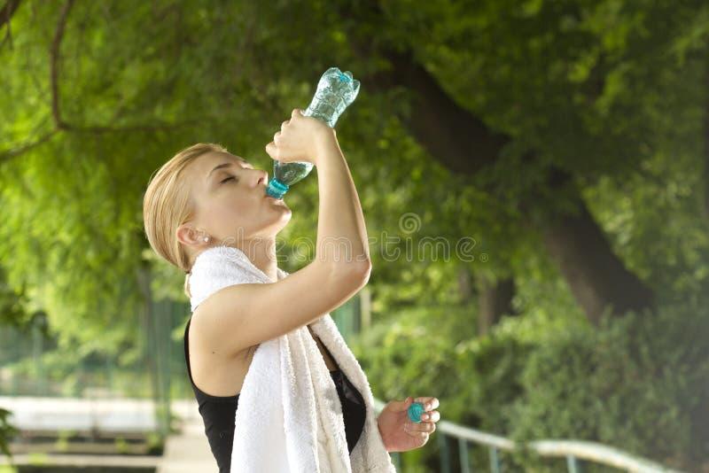 Trinkwasser der sportlichen Frau stockbild
