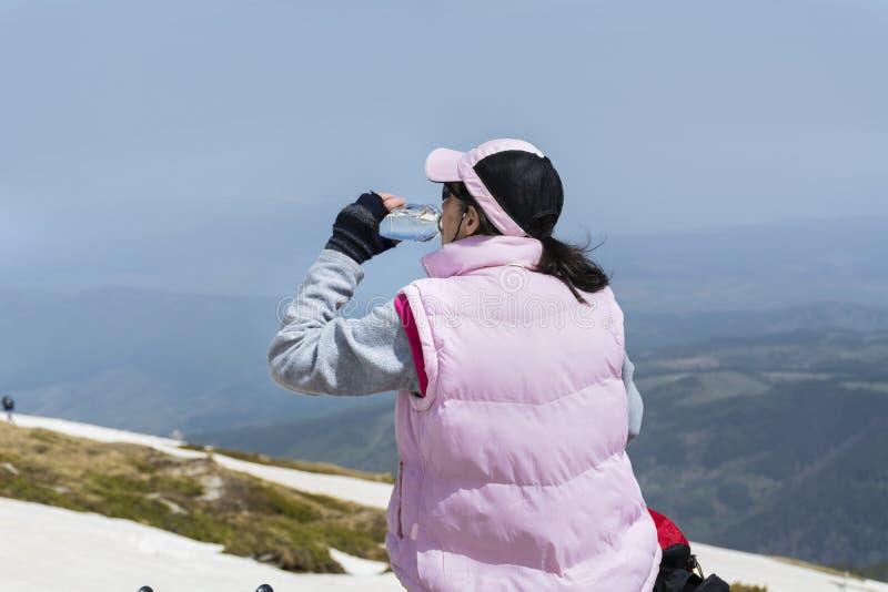 Trinkwasser der touristischen Frau in einem sonnigen Winterberg stockfotos