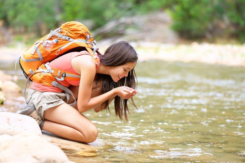 Trinkwasser der Wandererfrau vom Flussnebenflusswandern lizenzfreies stockbild