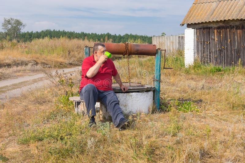Trinkwasser des älteren Mannes, das auf einer Bank nahe einem alten Ziehbrunnen sitzt lizenzfreies stockbild