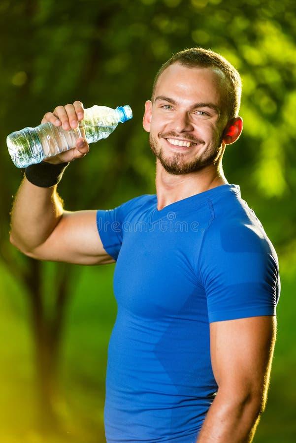 Trinkwasser des athletischen reifen Mannes von einer Flasche stockbilder