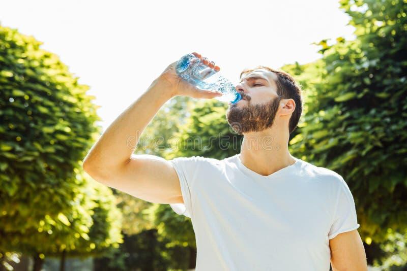 Trinkwasser des erwachsenen Mannes von einer Flasche draußen stockfoto