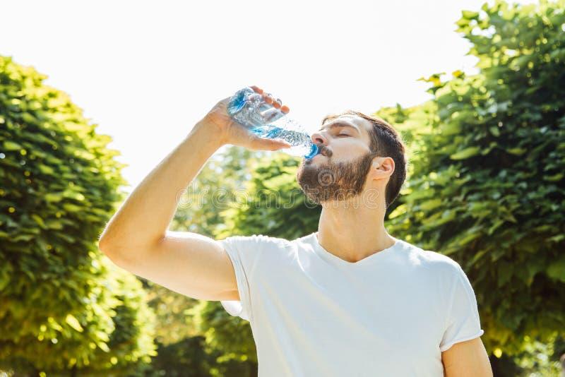 Trinkwasser des erwachsenen Mannes von einer Flasche draußen lizenzfreie stockbilder