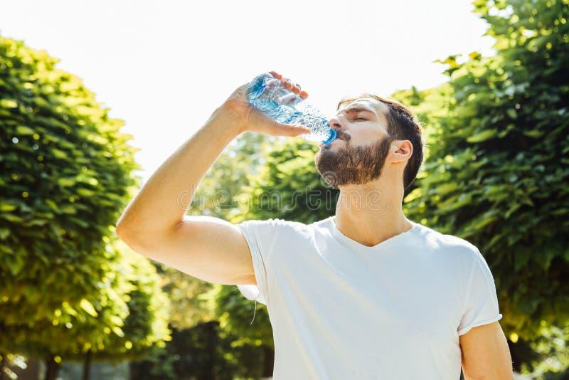 Trinkwasser des erwachsenen Mannes von einer Flasche draußen stockfotografie