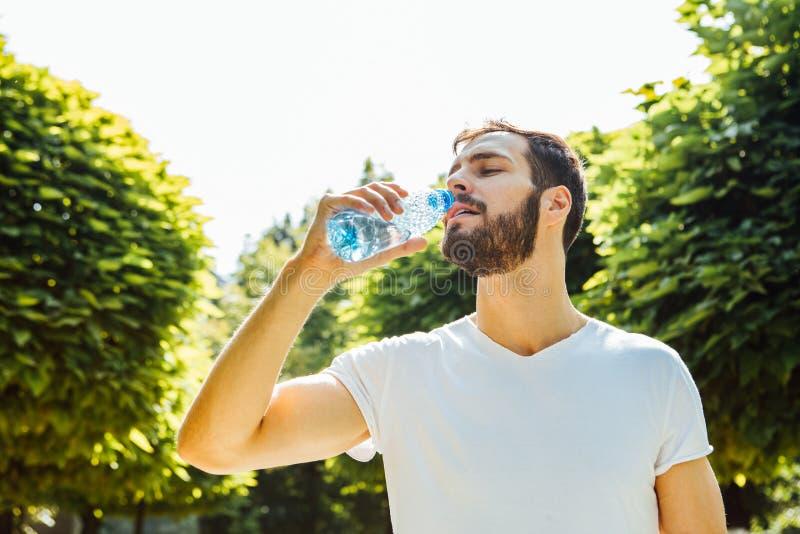 Trinkwasser des erwachsenen Mannes von einer Flasche draußen stockfotos