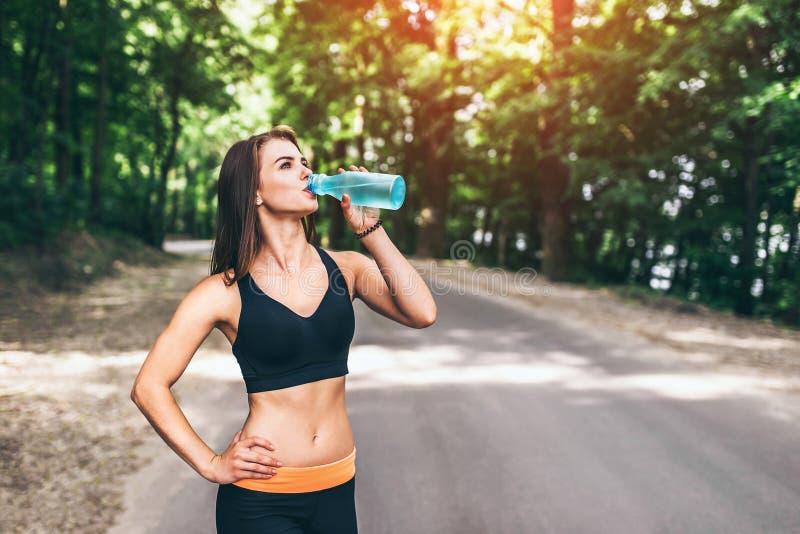 Trinkwasser des jungen Eignungsmädchens im Park stockfotos
