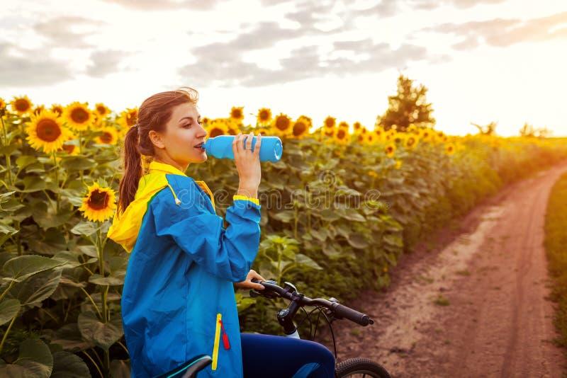 Trinkwasser des jungen glücklichen Frauenradfahrers, nachdem Fahrrad im Sonnenblumenfeld gefahren worden ist Sommer-Sport-T?tigke lizenzfreie stockfotos