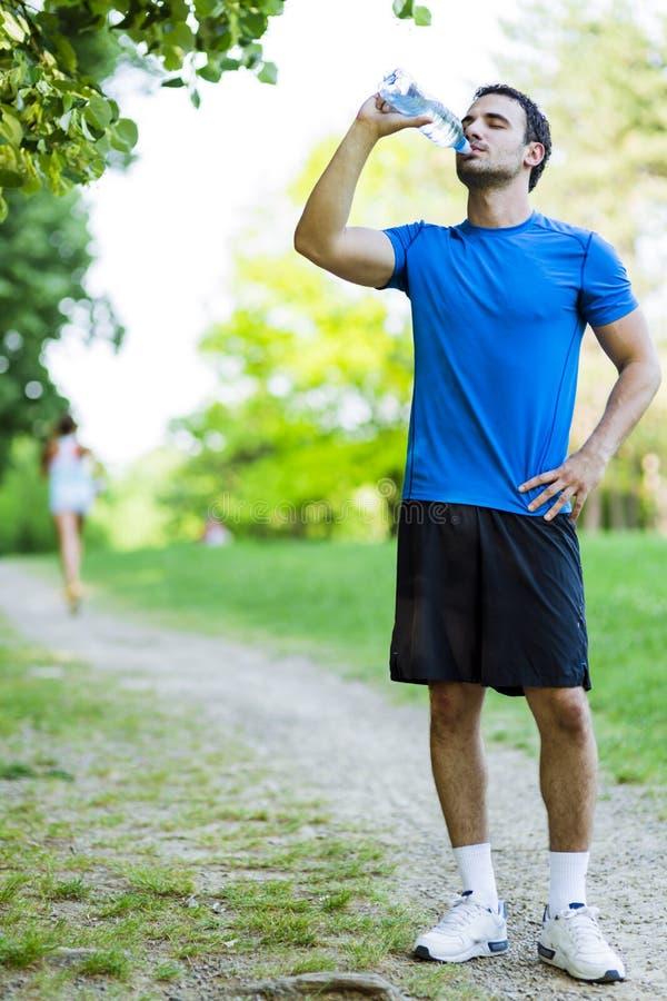 Trinkwasser des jungen männlichen Athleten lizenzfreies stockfoto