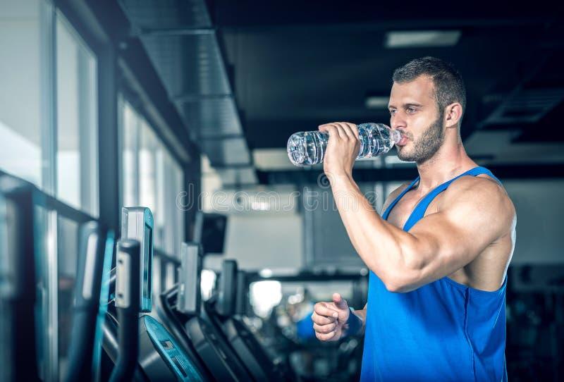 Trinkwasser des jungen Mannes in der Turnhalle lizenzfreie stockbilder
