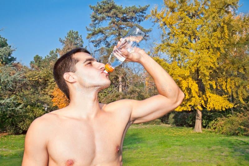 Trinkwasser des jungen Mannes im Herbstpark lizenzfreie stockfotos