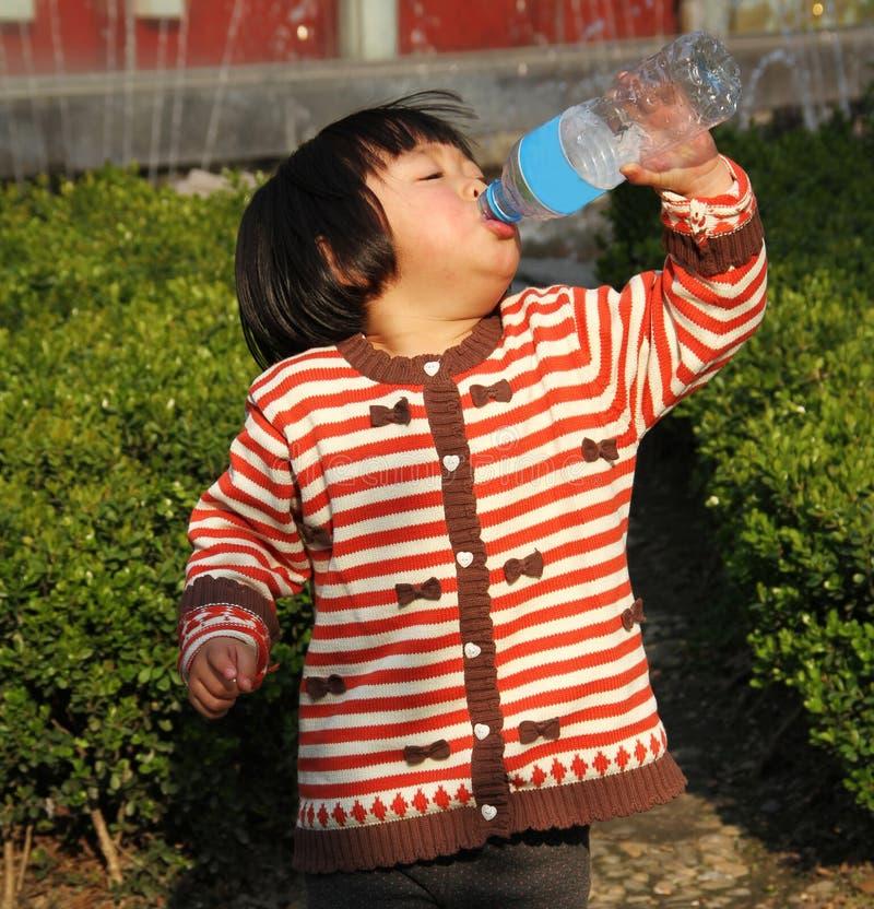 Trinkwasser des kleinen Mädchens stockbild