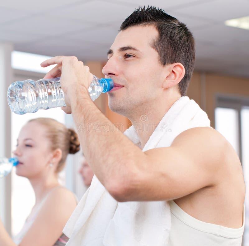 Trinkwasser des Mannes und der Frau nach Sport in der Turnhalle stockbild