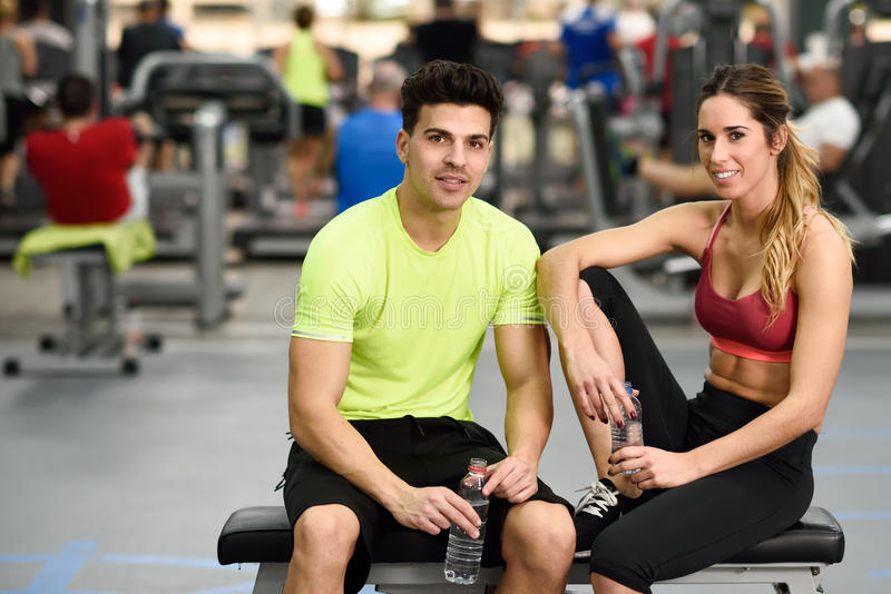 Trinkwasser des Mannes und der Frau nach Training stockfotos