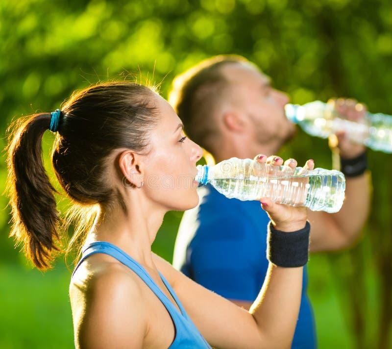 Trinkwasser des Mannes und der Frau von der Flasche nachher lizenzfreies stockfoto