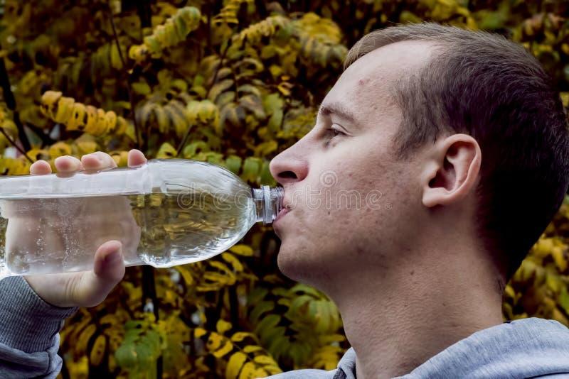 Trinkwasser des Mannes von einer Flasche draußen stockfotografie