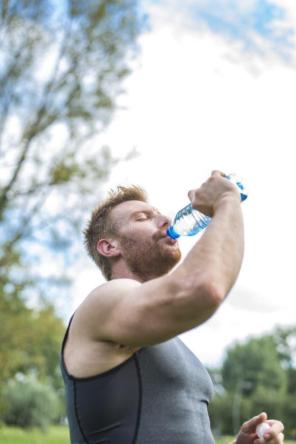 Trinkwasser des Mannes von einer Flasche draußen stockbild