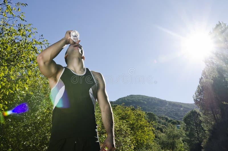 Trinkwasser des Sportlers mit sunflare lizenzfreie stockfotografie