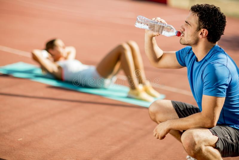 Trinkwasser des sportlichen Mannes w?hrend junge Frau, die ?bung im Th tut lizenzfreies stockfoto