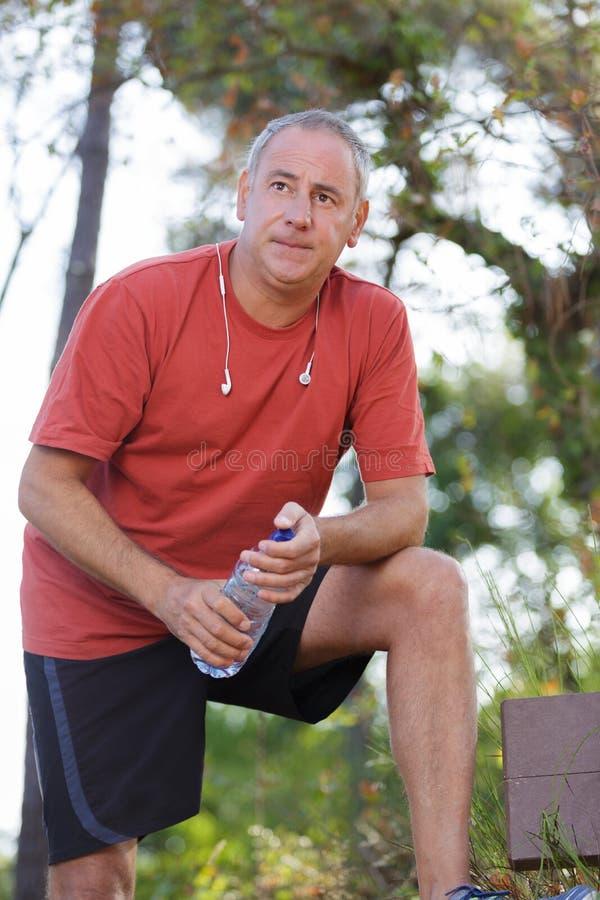 Trinkwasser von mittlerem Alter nach Training stockfotos