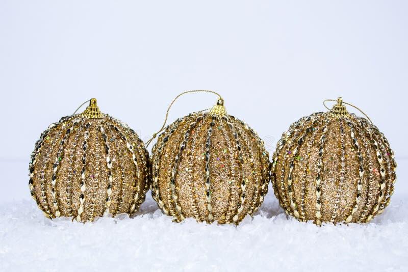 Trio av guld- prydnader royaltyfri bild