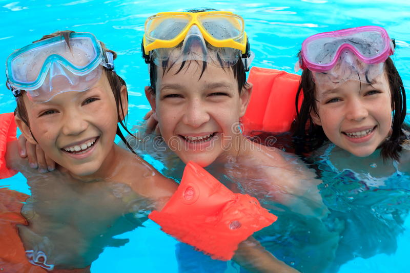 Trio of Happy Children in Swimming Pool. Three friends with swim floats smiling in swimming pool on vacation stock photos