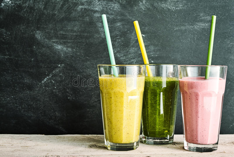 Trio of healthy fruit and vegetable smoothies. Berry, kale and banana and almond - with straws on a rustic wooden table with slate background with copy space stock image