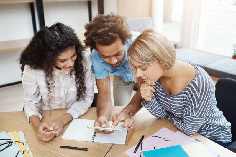 Trio jonge ondernemers die van nieuw startproject samenwerken Jongeren die in bibliotheek het kijken zitten royalty-vrije stock foto's