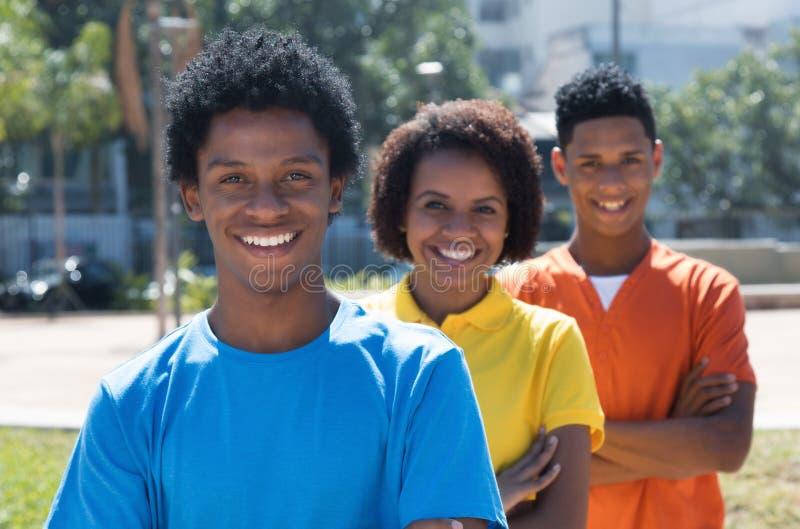 Trio lachende Afrikaanse Amerikaanse jonge volwassenen met gekruiste wapens stock foto's