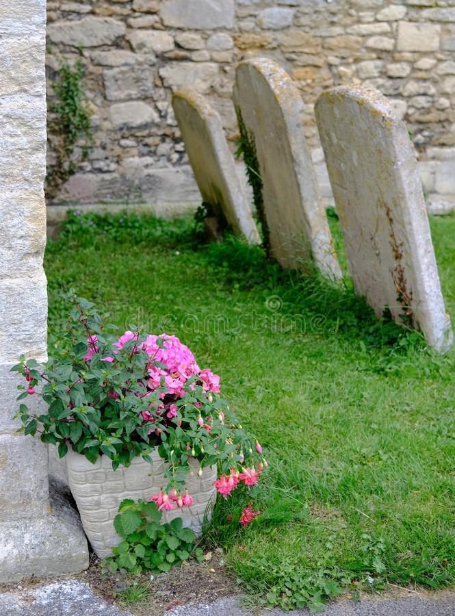 Trio of leaning gravestones seen near the porch of an old church, seen in summertime. stock photo