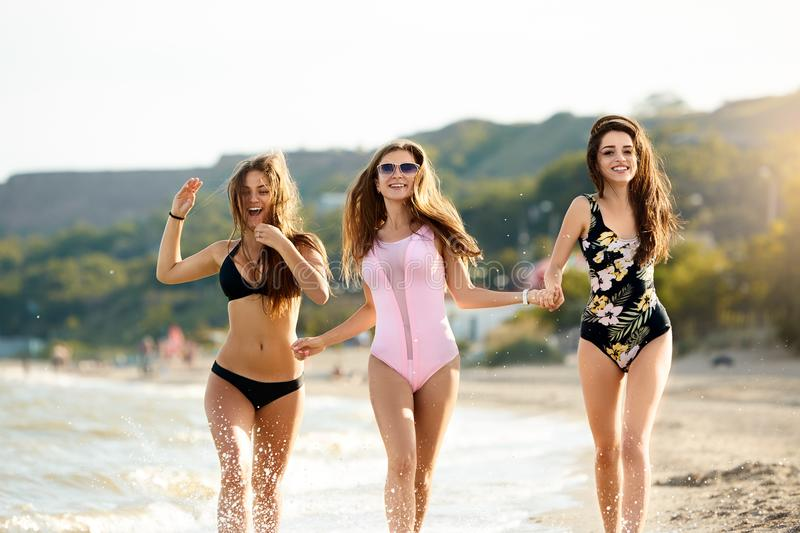 Trio mooie aantrekkelijke jonge vrouwen die op het strand dichtbij overzeese kust en plons watter dropplets lopen en royalty-vrije stock fotografie