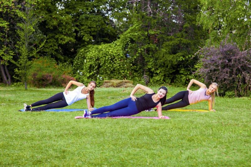 Trio mooie gezonde slijmerige vrouw die exersices op het groene gras in het park doen die, kant palnk, camera bekijken met royalty-vrije stock fotografie