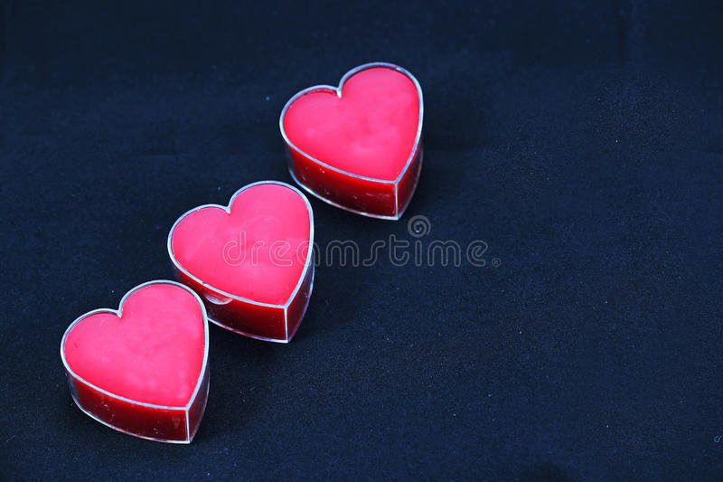 A Trio of Pink Hearts on a Black Background. A trio of poink hearts, on a black background, with space for your own text stock image