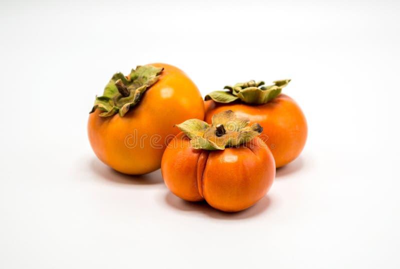 Three orange persimmons isolated on white stock image